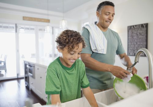 son and father doing dishes