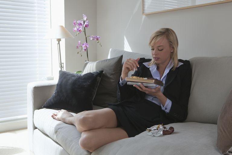 Woman sitting on couch eating chocolates