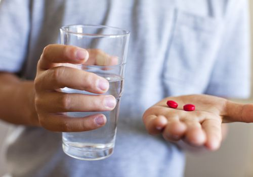 boy with pills in one hand and glass of water in other