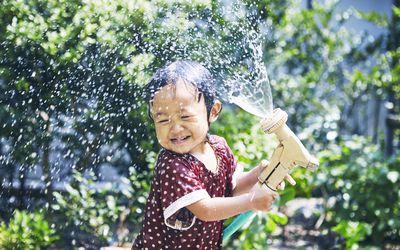 Little girl spraying water hose