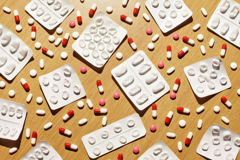 Prescription pills scattered on table with empty pill packets