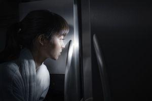 Mixed race woman peering into refrigerator at night