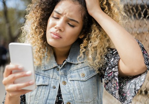 Unhappy Mixed Race woman texting on cell phone