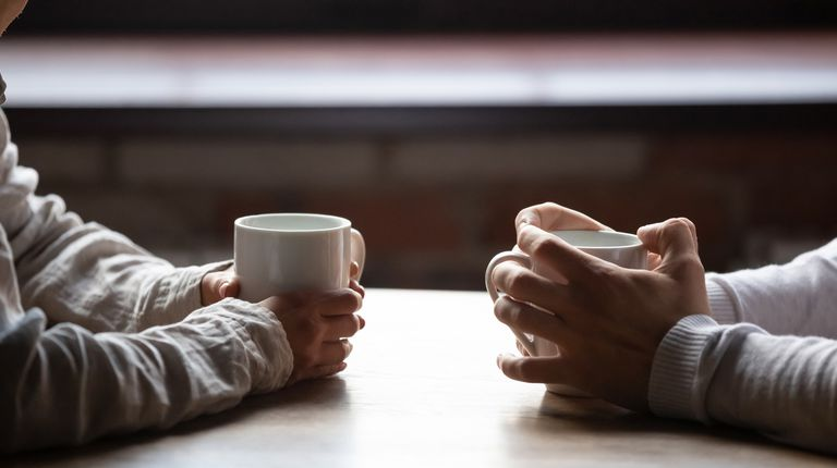 male and female hands holding coffee cups