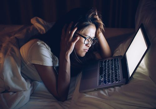 Distressed young woman looking at laptop in bed in the dark