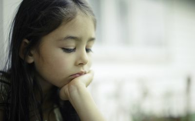Sad child looking down with her head in her hand