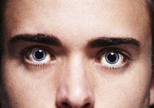 Close-up of a young man's intense, bloodshot eyes