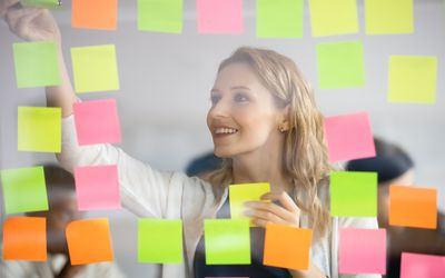 Smiling businesswoman removing sticky papers from scrum board