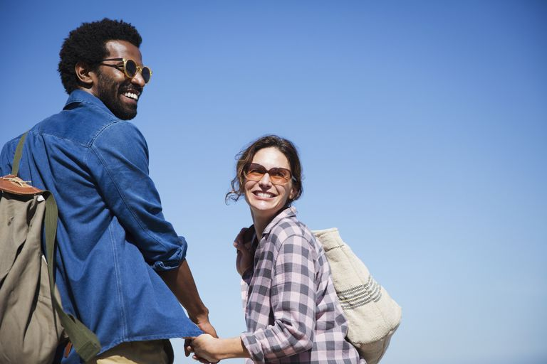 Portrait smiling, affectionate multi-ethnic couple holding hands below sunny summer blue sky