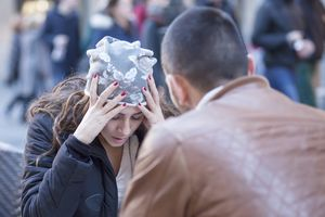 Woman with hands on head talking with man