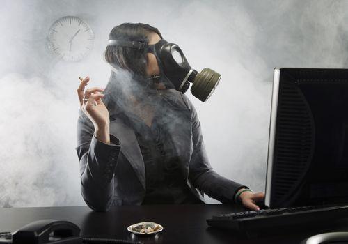 Woman holding smoking cigarette while wearing gas mask