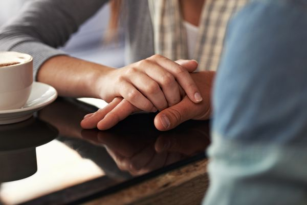 Woman comforting man (close-up of hands)