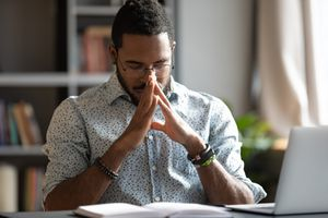 Young businessman doing deep breathing exercise at his desk