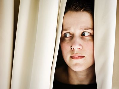 woman with agoraphobia peeking out from curtains