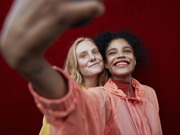 Two young women smiling and taking a selfie.