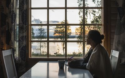 woman in a cabin looking out the window