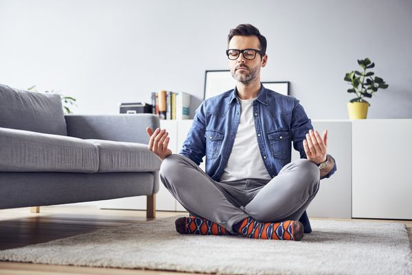 Relaxed man meditating at home