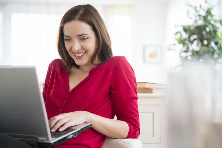 Woman using laptop computer, smiling