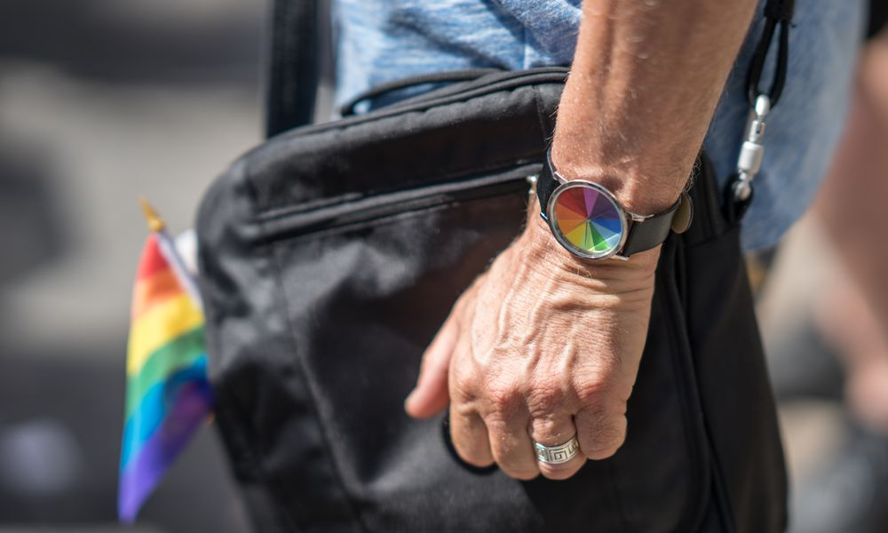 Man in wedding ring with rainbow watch and flag