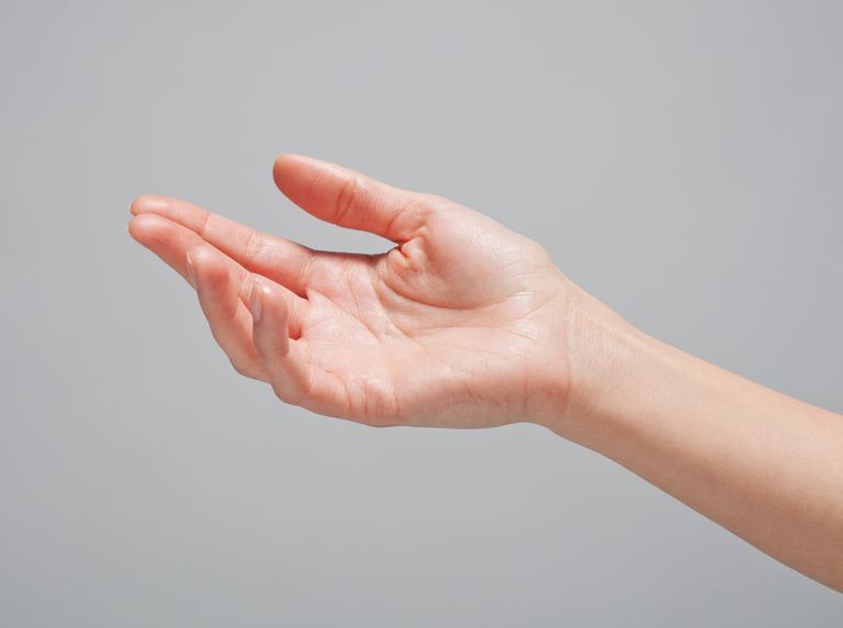 A hand reaching out in front of a grey background