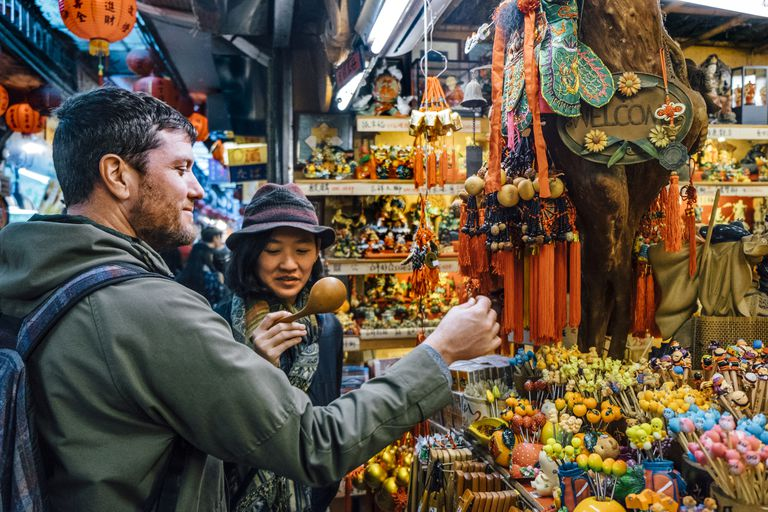 man and woman looking at trinkets while traveling