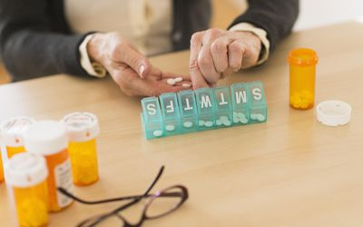 Woman sorting pills into a weekly organizer