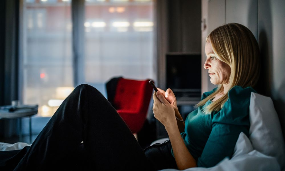 Businesswoman Reclining On Bed Using Smartphone