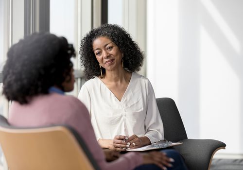 Adult counselor listens compassionately to client in bright windowed room