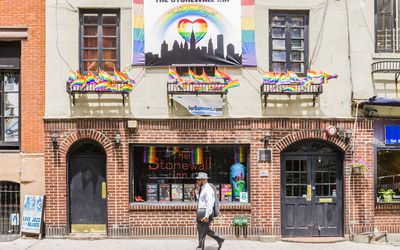 A person walks in front of the Stonewall Inn decorated in Pride decor.