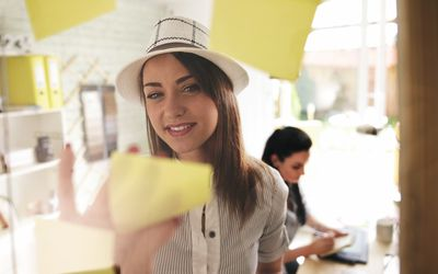 woman putting sticky note on wall