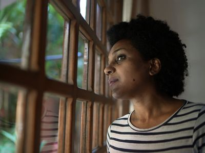 BIPOC immigrant looking out window
