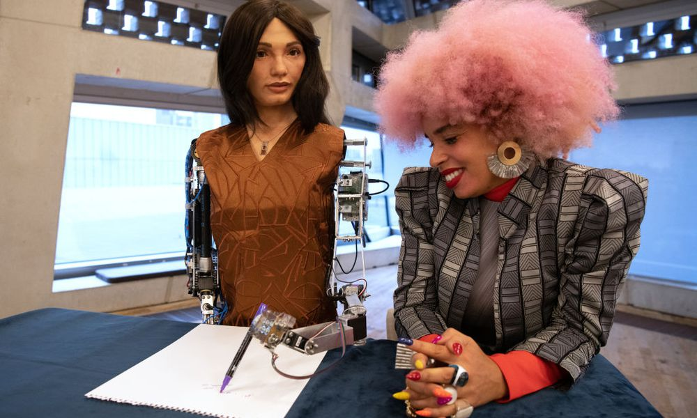 """Artist Sadie Clayton (R) is seen with """"Ai-Da"""", the first ultra-realistic robot artist."""