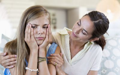 Woman persuading her upset daughter at home