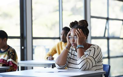 Worried student sitting with head in hands at desk