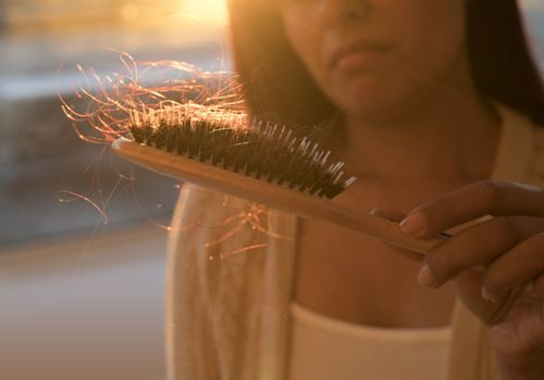 A woman holds a hair brush with a lot of hair in it.
