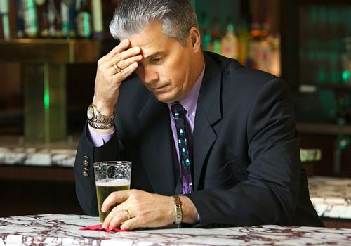 Businessman in bar with his hand on his head