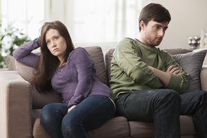 Caucasian couple arguing on sofa