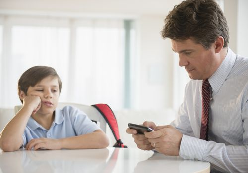 Dad on phone while sitting at table with son