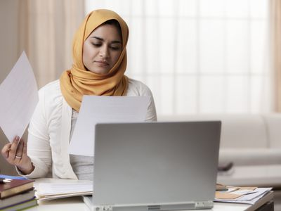 Mixed race woman in hijab looking at paperwork