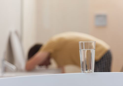 glass of water on counter with man vomiting in toilet in background