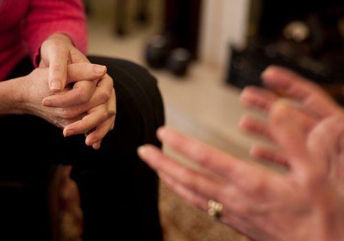 Woman's hands crossed next to man's hands gesturing