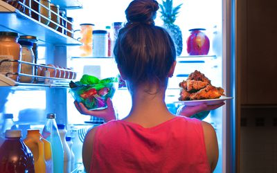 Woman pulling unwrapped food from fridge
