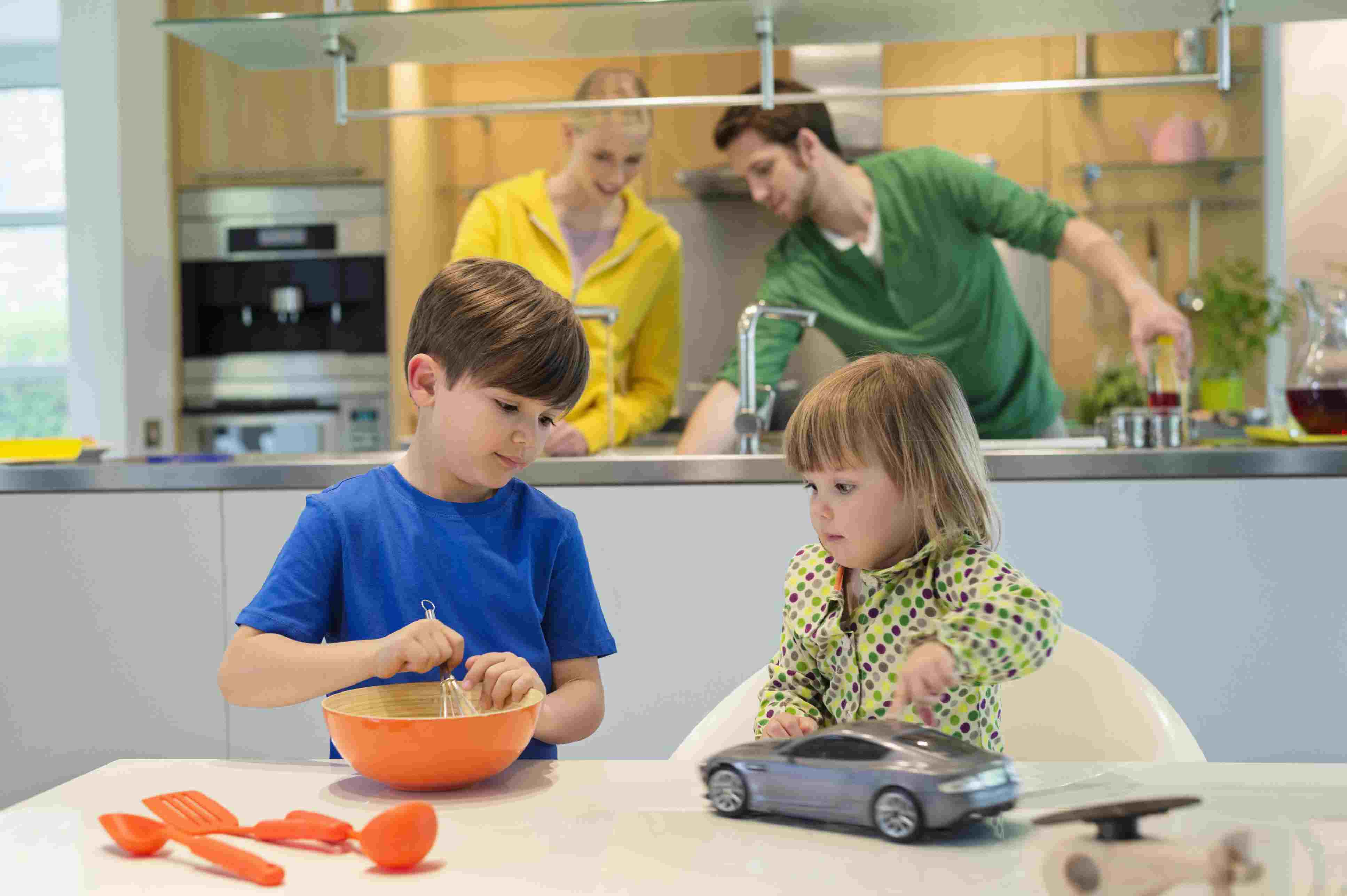 Mother, father, and two young children spending time together in the kitchen.