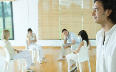 Group therapy session, man standing in foreground, smiling