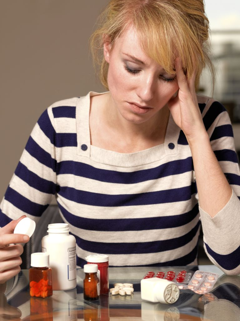 Girl contemplating an array of perscription drugs