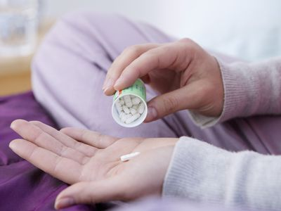 Woman dumping a pill into her hand