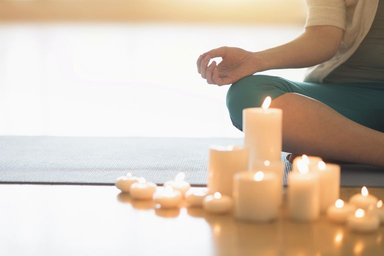 Woman meditating with candles.