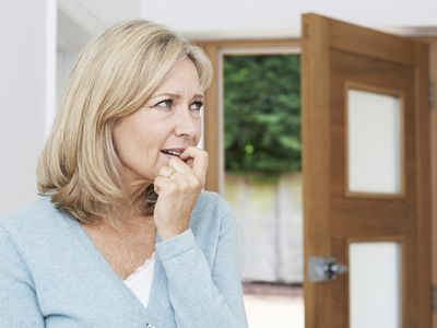 woman with agoraphobia at door afraid to go outside due to panic disorder