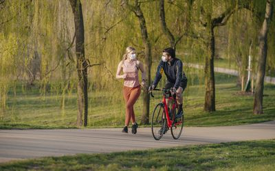 A woman jogs next to a man on a bike in a lush green park.