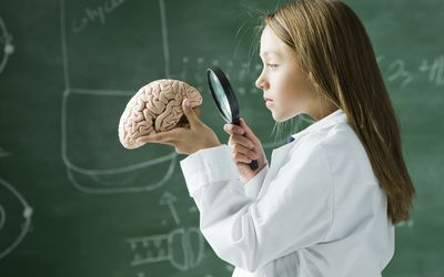 young girl in lab coat looking at brain with magnifying glass